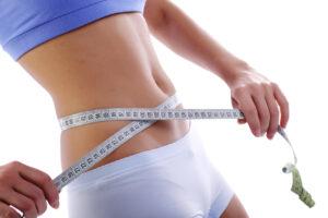 Measuring tape around slim beautiful waist.